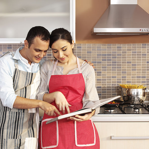 young couple in kitchen planning pasta meal